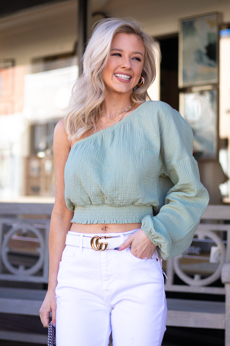 ANOTHER ONE SHOULDERED TOP JUST THIS TIME IN GREEN. THIS SHADE OF GREEN IS SO IN THIS SEASON AND WE THINK STYLED WITH LIGHT WASHED DENIM YOU WILL HAVE A WHOLE LOOK. -Taylor is wearing a size small -color: sage  -accordion stitching and stretch  -one shouldered  -lightweight fabric