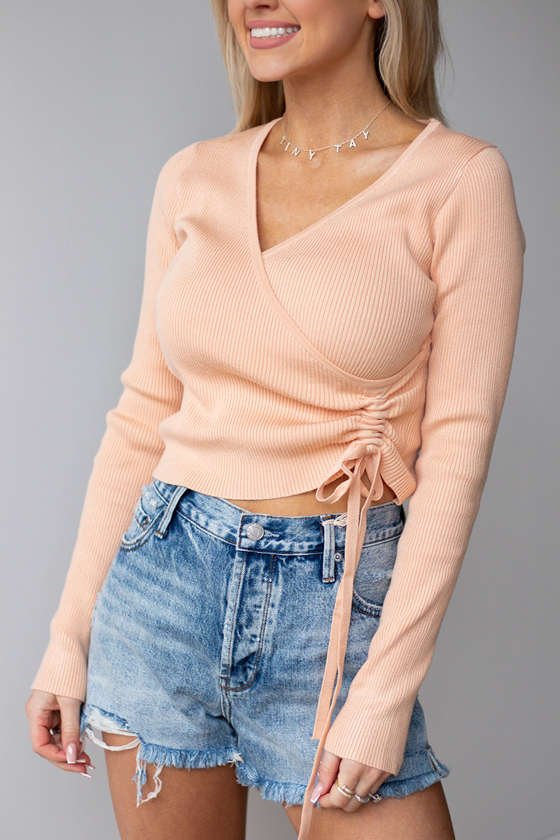 I MEAN YEAH LOOK OVER HERE. YOU ARE SURE TO CATCH SOME CUTIES IN THIS FUN APRICOT COLOR! WE LOVE THE SASSY TIE DESIGN AND ULTRA COMFY SWEATER MATERIAL!! -Taylor is wearing a size small -color: peachy/apricot  -wrap style top -tie side design  -adjustable amount of scrunch to tie -ribbed sweater material