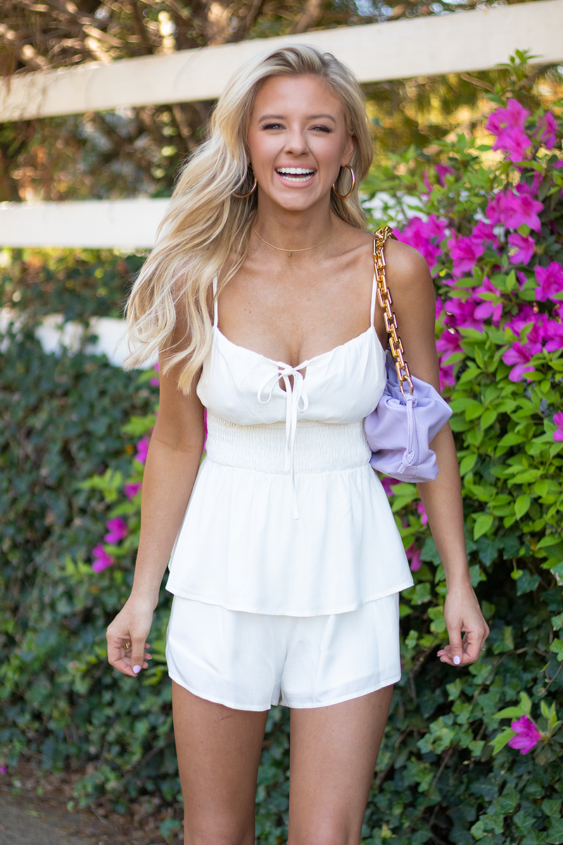 THIS ROMPER MAKES YOU ENJOY THE DAY. IT'S SO LIGHT AND FUN THAT YOU BASICALLY HAVE TO. WEAR THIS WHITE ROMPER FOR GRADUATIONS, EVENTS, OR JUST EVERYDAY STYLING.  -Taylor is wearing the size small -color: white -tiered flowy design  -accordion elastic waistband  -tie top neckline