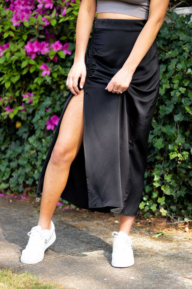 Y'ALL LOVED IT IN GREEN SO WE HAD TO BRING IT IN A NEUTRAL COLOR. THIS BLACK SCRUNCH MIDI SKIRT IS GOING TO BE SOMETHING YOU WILL WEAR WITH EVERYTHING..TRUST US. -Taylor is wearing the size small -color: Black  -scrunch design allows for you to adjust skirt to your liking -pair with a little crop top and sandals for an adorable look