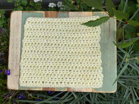A square of crocheted fabric in pale yellow
