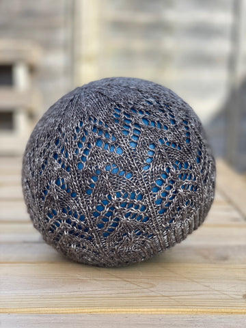 A knitted lace beanie hat on a ball