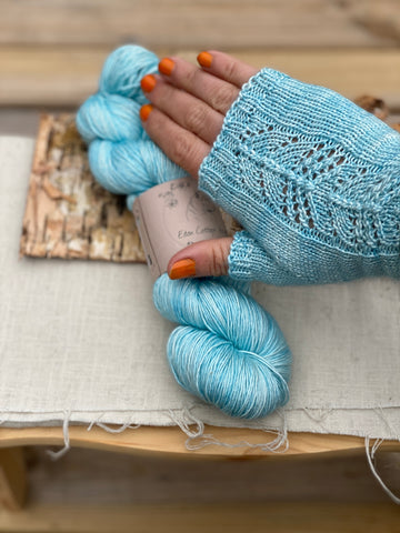 A knitted fingerless mitten on a hand, which is holding a skein of yarn