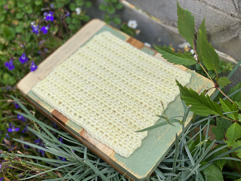 a pale yellow square of crocheted fabric
