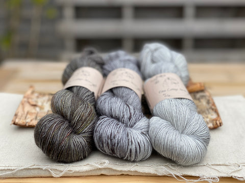 three skeins of hand dyed yarn in various shades of grey
