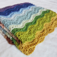 A folded crochet blanket featuring a striped ripple stitch pattern. The blanket uses all twenty colours of Milburn DK but only some of these colours are visible. The pattern is Elysium by Sarah Alderson