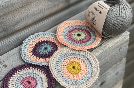 Four crocheted circles are sat on a wooden shelf, in colours of aubergine, beige, peach, pink, silver, yellow, and sage green. They are next to a steely grey ball of Milburn DK yarn.