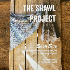 Shawl Project Book Five resting on a wooden bench