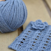Blue yarn alongside a knitted square