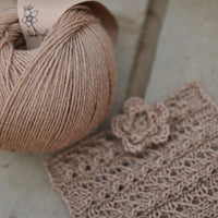 Golden brown yarn alongside a knitted square