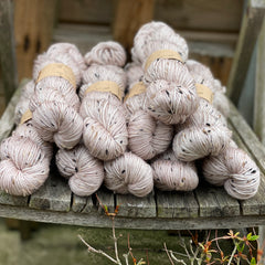 Ten skeins of soft beige yarn, colourway Stone, are sat on a wooden chair and viewed from the front. The yarn features flecks of brown, black and cream fibres throughout the skeins.