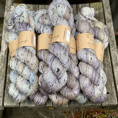 Ten skeins of variegated yarn in a Cottage Original colourway are sat on a wooden chair. The yarn is a mix of purple, soft brown, beige and hints of light blue. The yarn features flecks of brown, black and cream fibres throughout the skeins.