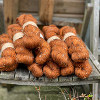 Ten skeins of orangey-red yarn, colourway Rust, are sat on a wooden chair and viewed from the front. The yarn features flecks of brown, black and cream fibres throughout the skeins.