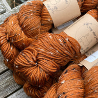 Close up image of orangey-red yarn, colourway Rust, sat on a wooden chair. The yarn features flecks of brown, black and cream fibres throughout the skeins which are clearly shown in this image.