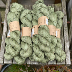 Ten skeins of green yarn, colourway Coppice, are sat on a wooden chair. The yarn features flecks of brown, black and cream fibres throughout the skeins.