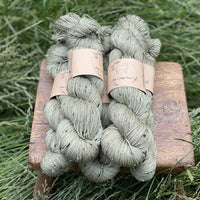 Five skeins of greenish brown yarn, colourway Hedgerow, are sat on a wooden stool surrounded by grass. The yarn features flecks of brown, black and cream fibres throughout the skeins.