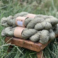 Five skeins of greenish brown yarn, colourway Hedgerow, are sat on a wooden stool surrounded by grass and viewed from the side. The yarn features flecks of brown, black and cream fibres throughout the skeins.