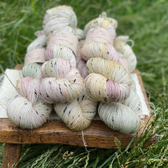 Five skeins of variegated yarn, colourway Cottage Garden, are sat on a wooden stool surrounded by grass. The yarn is a mix of pale pink, cream, yellow and green. The yarn features flecks of brown, black and cream fibres throughout the skeins.