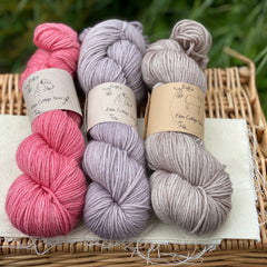 Three skeins of yarn are sat on a wicker basket. The colours from left to right are Dianthus, Dusk and Bark. The yarns are shades of pink, purple and brown.