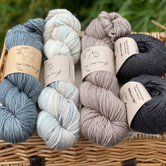 Three skeins of yarn and two balls of Milburn DK are sat on a wicker basket. The colours from left to right are Pennine Mist, Snowy Owl, Bark and Charcoal. The yarns are shades of blue, brown and black with a variegated skein of natural with washes of brown and speckles of blue.
