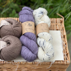 Two skeins of yarn and two balls of Milburn DK are sat on a wicker basket. The colours from left to right are Compost, Thunder and Snow Leopard. The colours are shades of brown, purple and a variegated skein of cream with black speckles.