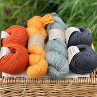 Two skeins of yarn and four balls of Milburn DK are sat on a wicker basket. The colours from left to right are Crocosmia, Cloudberry, Ash and Charcoal. The colours are shades of orange and grey.
