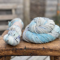 Variegated blue and cream yarn with black, brown and cream neps running through it.