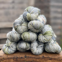 Variegated green, grey and cream yarn with black, brown and cream neps running through it.