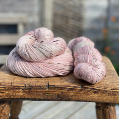 Pink yarn with black, brown and cream neps running through it.