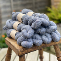 Blue yarn with black, brown and cream neps running through it.