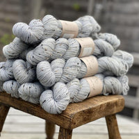 Pale blue yarn with black, brown and cream neps running through it.