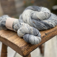 Variegated grey and cream yarn with black, brown and cream neps running through it.
