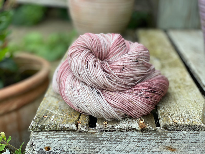 Variegated pink and cream yarn with black, brown and cream neps running through it.