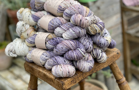 Variegated purple, cream and yellow yarn with black, brown and cream neps running through it.