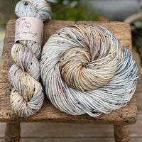 Variegated brown, grey and cream yarn with black, brown and cream neps running through it.