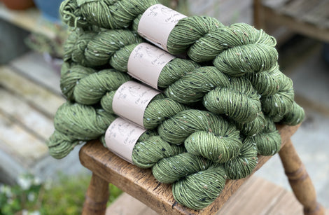 Green yarn with black, brown and cream neps running through it.