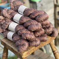 Brown yarn with black, brown and cream neps running through it.