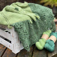 Echoing Green shawl alongside the yarns in the kit
