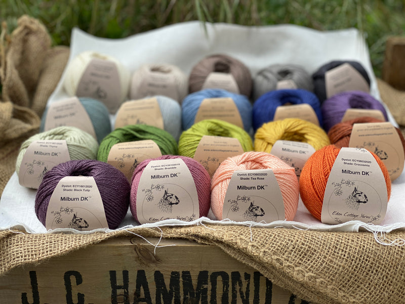 19 balls of yarn are arranged in three rows of five balls and one row of four in the foreground. The yarn is resting on a white piece of fabric in a jute lined wooden box. From left to right, the colours in the top row are Natural, Wicker, Compost, Steel and Charcoal. The colours in the second row are Catmint, Rain, Estuary, Night Sky and Damson. The colours in the third row are Thyme, Moss, Fern, Harvest Gold and Rust. The colours in the bottom row are Black Tulip, Bramble, Tea Rose and Crocosmia.