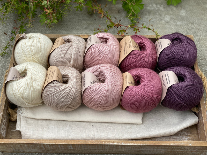 10 balls of yarn are sat in a wooden tray, there are two balls of each colour. The colours from left to right are Natural, Wicker, Althaea, Bramble and Black Tulip. The yarns create a fade effect from natural cream, through pink to dusky purple.
