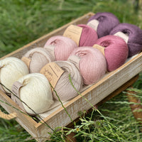 10 balls of yarn are sat in a wooden tray on a stool, sitting in grass. There are two balls of each colour. The colours from left to right are Natural, Wicker, Althaea, Bramble and Black Tulip. The yarns create a fade effect from natural cream, through pink to dusky purple.