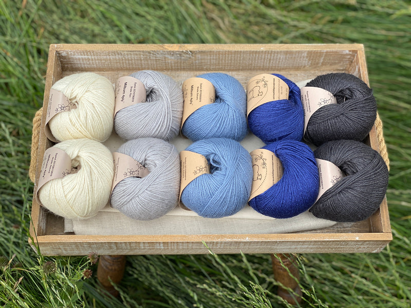 10 balls of yarn are sat in a wooden tray surrounded by grass. There are two balls of each colour. The colours from left to right are Natural, Rain, Estuary, Night Sky and Charcoal. The yarns create a fade effect from natural cream through shades of blue, ending in dark grey.