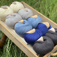 10 balls of yarn are sat in a wooden tray surrounded by grass. There are two balls of each colour. The colours from top left to bottom right are Natural, Rain, Estuary, Night Sky and Charcoal. The yarns create a fade effect from natural cream through shades of blue, ending in dark grey.