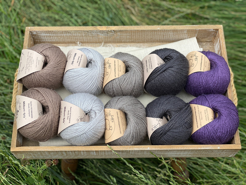 10 balls of yarn are sat in a wooden tray surrounded by grass. There are two balls of each colour. The colours from left to right are Compost, Rain, Steel, Charcoal and Damson. The yarns create a palette of greys with brown and purple accents.