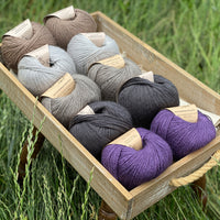 10 balls of yarn are sat in a wooden tray surrounded by grass. There are two balls of each colour. The colours from top left to bottom right are Compost, Rain, Steel, Charcoal and Damson. The yarns create a palette of greys with brown and purple accents.