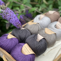 10 balls of yarn are sat in a wooden tray. There are two balls of each colour. The colours from top right to bottom left are Compost, Rain, Steel, Charcoal and Damson. The yarns create a palette of greys with brown and purple accents. Purple flowers of a buddleja are visible in the picture complementing the purple of the Damson colourway.