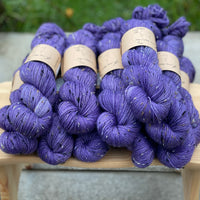 Purple yarn with black, brown and cream neps running through it.