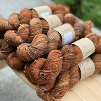 Variegated brown yarn with cream, brown and black neps.