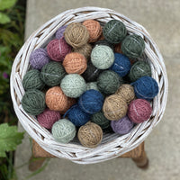 A small round white wicker basket containing Yarnlings (small balls of yarn) in a variety of colours including blue, grey, green, brown, pink and purple. The basket sits on a wooden stool on concrete paving..