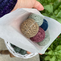 A glassine bag containing Yarnlings is held in the palm of a hand. The bag contains five DK weight Yarnlings in a lucky dip of colours. This bag has brown, purple, dark blue and pale green yarns.